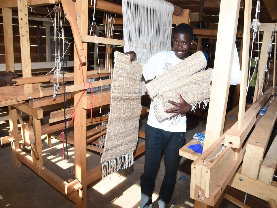 A trainee cerebrates acquisition of rug weaving skills at TEXFAD